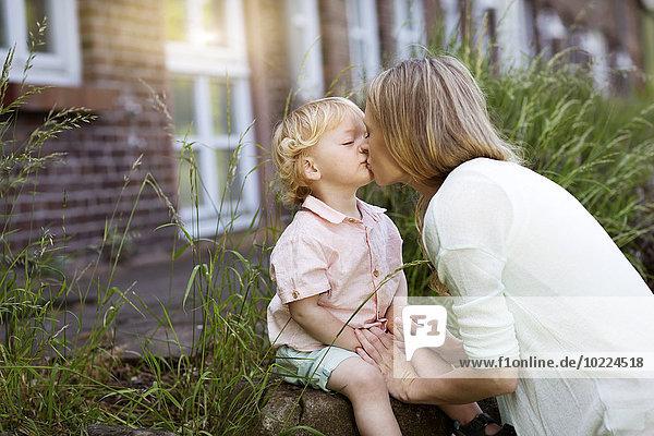 Mutter küsst ihren kleinen Sohn vor dem Haus.