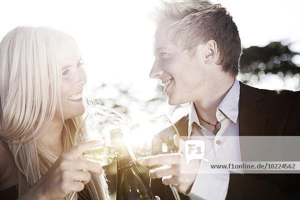 Fröhliches junges Paar im Freien beim Weintrinken