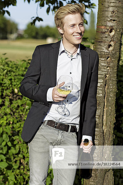 Smiling young man outdoors with wine glass and bottle