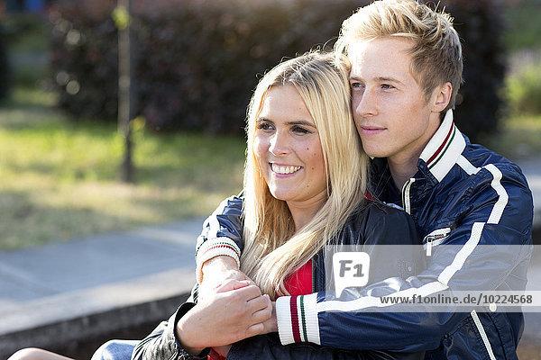 Lächelndes junges Paar  das sich im Freien umarmt.