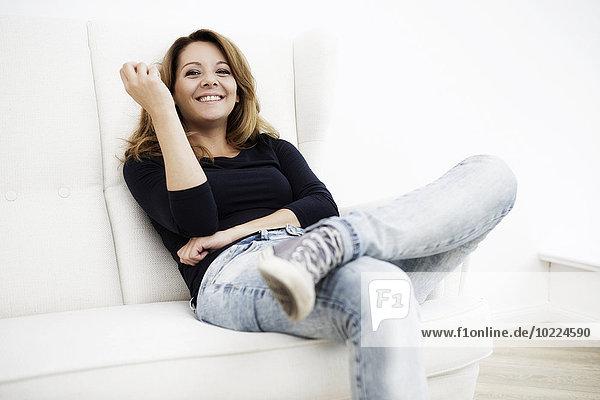 Porträt einer lächelnden Frau  die auf einer weißen Couch sitzt.
