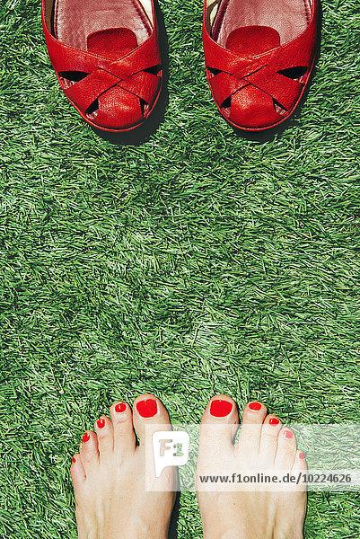 Barfuß-Frauen mit rot lackierten Nägeln neben einem Paar roter Schuhe  auf dem grünen Gras