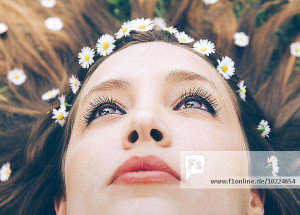 Junge Frau auf Gras liegend mit Gänseblümchen im Haar  Nahaufnahme