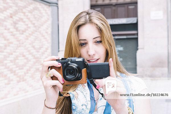 Spanien  Barcelona  junge Frau beim Fotografieren mit Digitalkamera