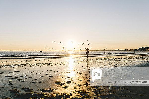 Frankreich  Pornichet  Silhouette der laufenden Frau am Strand bei Sonnenuntergang