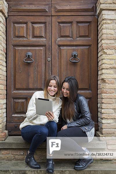Italien  San Gimignano  zwei junge Frauen  die vor der Eingangstür sitzen und ein digitales Tablett benutzen.