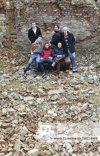 Gruppenbild von sechs Freunden umgeben von zerbrochenen Steinen