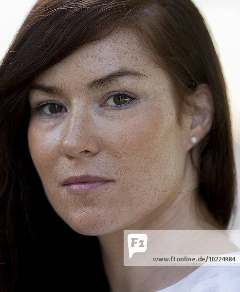 Porträt einer Frau mit braunen Haaren und Sommersprossen  Nahaufnahme