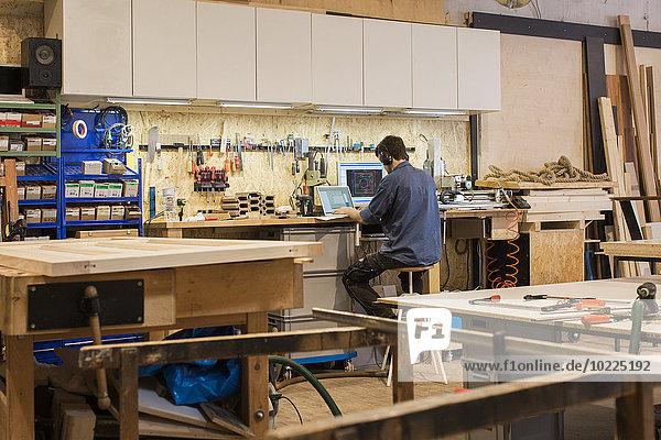 Schreiner bei der Arbeit mit dem Computer in der Werkstatt