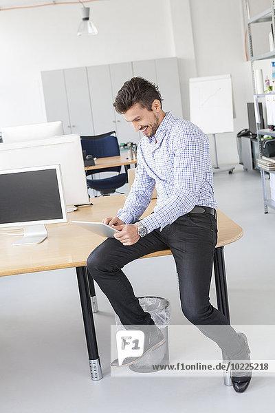 Lächelnder Geschäftsmann mit digitalem Tablett im Büro