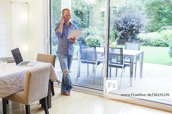 Lächelnder Mann mit Dokumenten beim Telefonieren mit dem Smartphone zu Hause