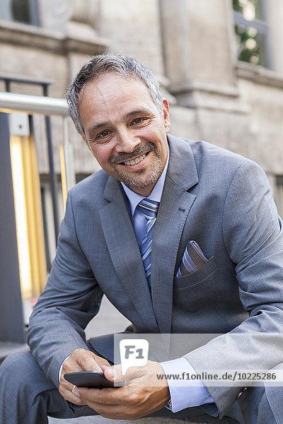Porträt eines lächelnden Geschäftsmannes im grauen Anzug