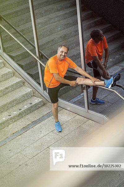 Germany  Stuttgart  portrait of smiling jogger stretching his leg