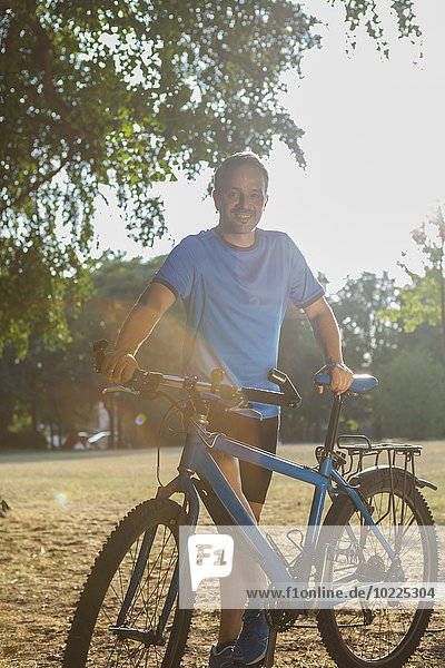 Portrait of smiling man standing in a park with bicycle