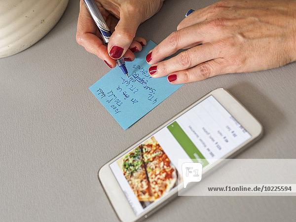 Frau schreibt Rezept auf einen Zettel