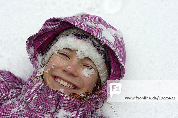 Portrait of smiling girl lying on snow