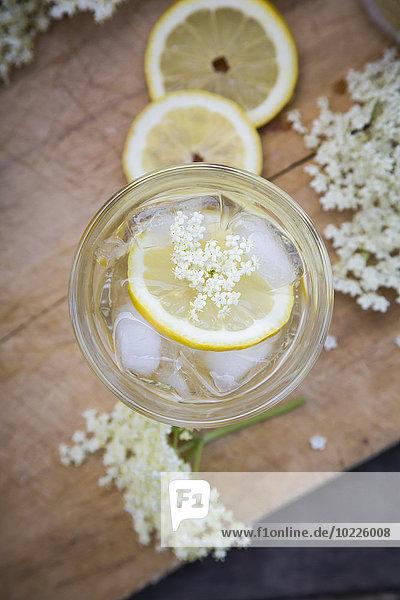 Glas Holunderblütensirup mit Eiswürfeln und Zitronenscheiben Glas Holunderblütensirup mit Eiswürfeln und Zitronenscheiben