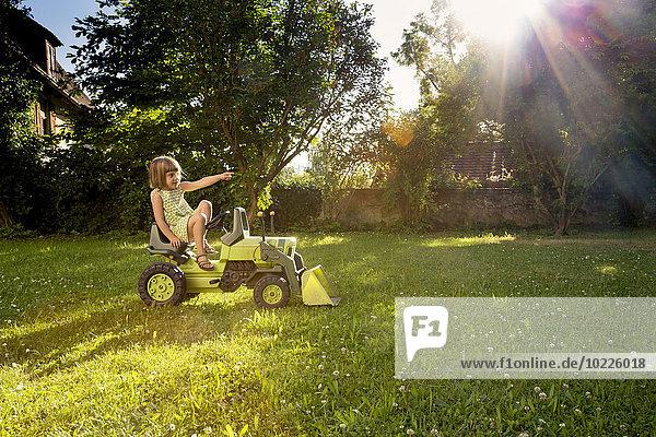 Kleines Mädchen spielt mit Spielzeugtraktor im Garten