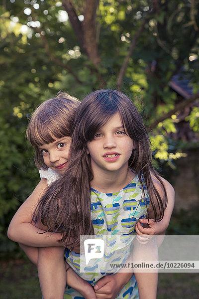 Girl giving her little sister a piggy back in the garden