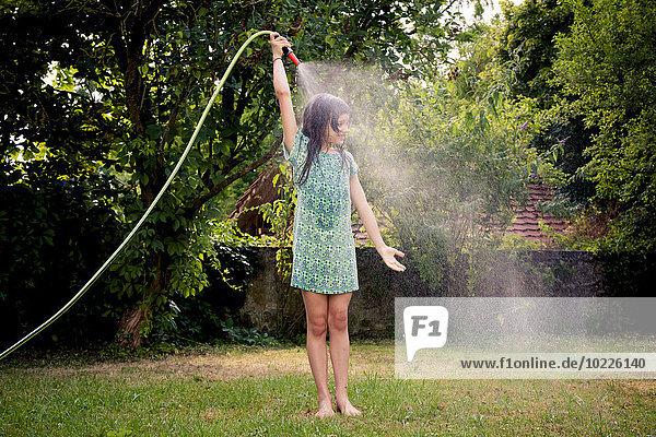 Mädchen kühlt sich mit Gartenschlauch ab Mädchen kühlt sich mit Gartenschlauch ab