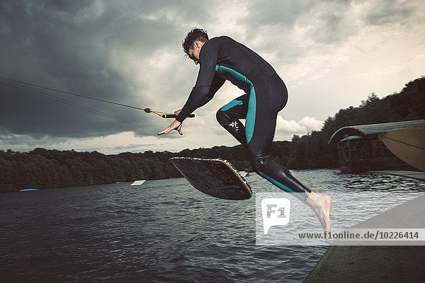 Junge Wakeboarder springen in der Luft