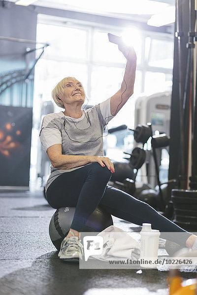 Seniorenfrau im Fitnessstudio mit einem Selfie