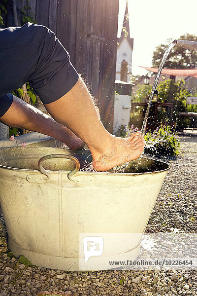 Mann beim Fußbad im Garten Mann beim Fußbad im Garten
