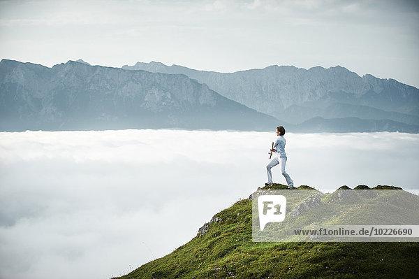 Österreich  Kranzhorn  Mittlere erwachsene Frau beim Stockkampf auf dem Berggipfel