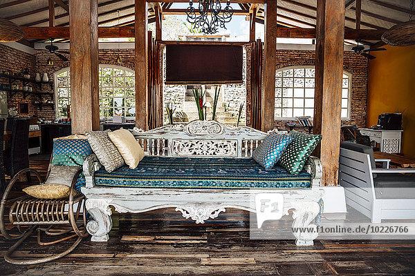 Indonesien  Bali  klassische indonesische Holzliege in einer Ferienvilla