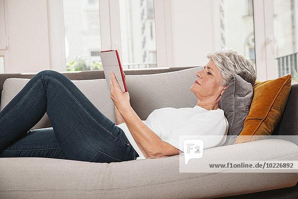 Reife Frau entspannt mit digitalem Tablett auf der Couch im Wohnzimmer