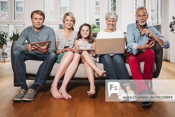 Gruppenbild von drei Generationen Familie mit verschiedenen digitalen Geräten auf einer Couch