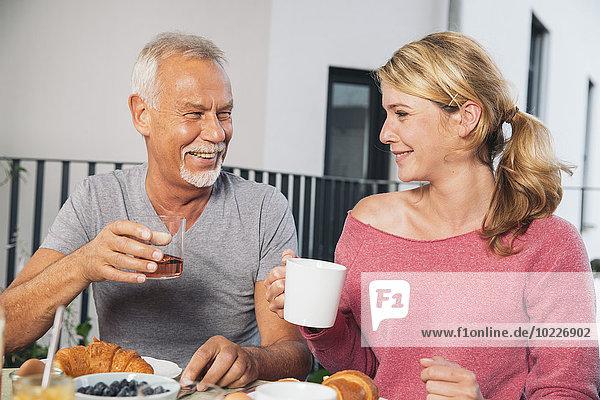 Vater und erwachsene Tochter beim Frühstück auf dem Balkon