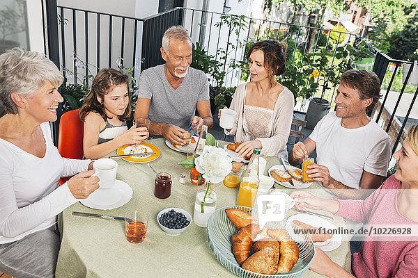 Familie beim Frühstück auf dem Balkon