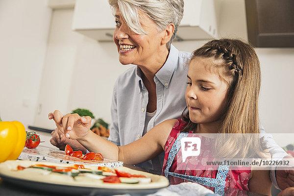 Kleines Mädchen und ihre Großmutter bereiten Pizza zu.