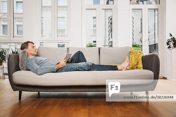 Mann entspannt mit digitalem Tablett auf der Couch im Wohnzimmer