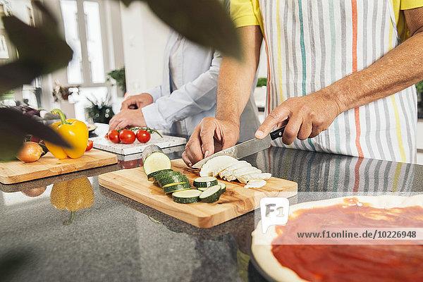 Paare schneiden Gemüse in der Küche