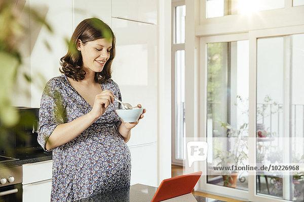 Schwangere mit Müslischale in der Küche