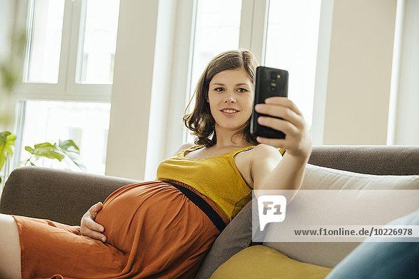 Schwangere Frau  die zu Hause einen Selfie mit Smartphone auf der Couch hat.