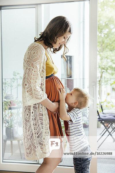 Kleiner Junge  der zu Hause den Bauch seiner schwangeren Mutter küsst.