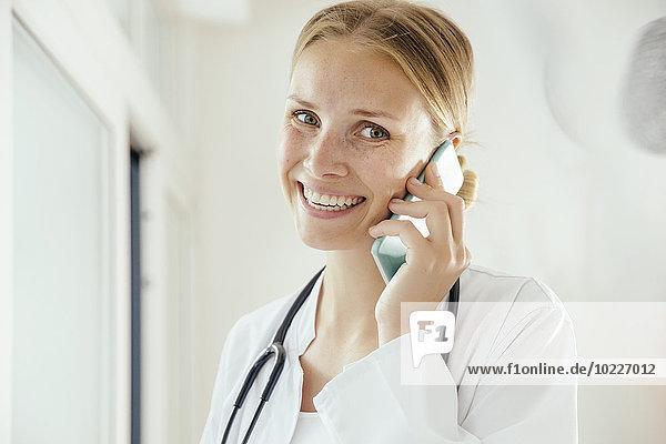 Lächelnde Ärztin im Gespräch mit dem Handy