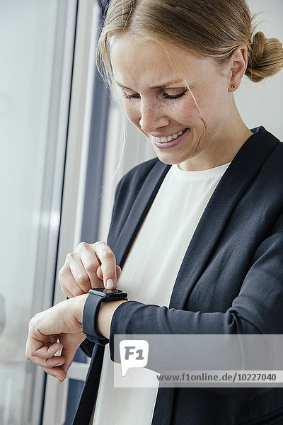 Lächelnde junge Geschäftsfrau bei der Überprüfung ihrer intelligenten Uhr