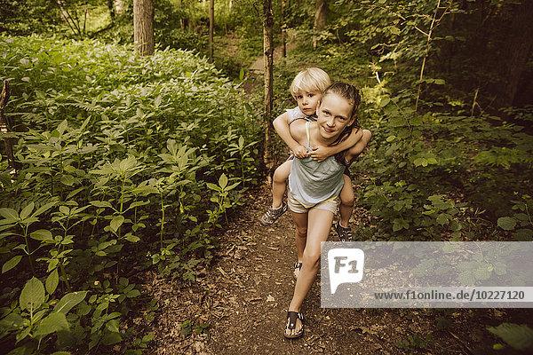 Girl carrying little boy piggyback through a forest