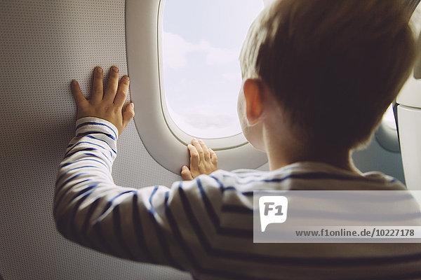 Kleiner Junge schaut aus dem Fenster  während er in einem Flugzeug fliegt. Kleiner Junge schaut aus dem Fenster, während er in einem Flugzeug fliegt.