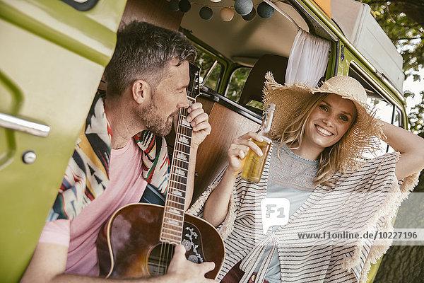 Glückliches Paar im Lieferwagen beim Musizieren