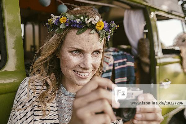 Hippie-Frau mit analoger Kamera vor dem Van