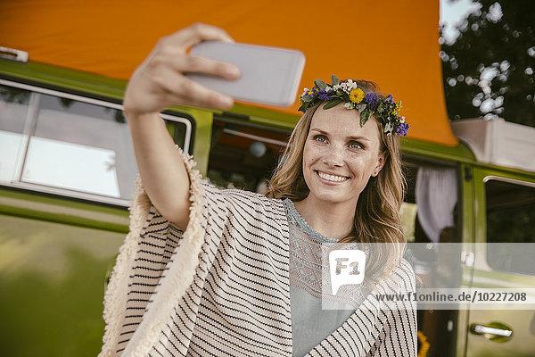 Hippie-Frau  die einen Selfie vor dem Van nimmt
