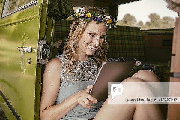 Fröhliche junge Frau schaut auf Tablet-Computer im Lieferwagen
