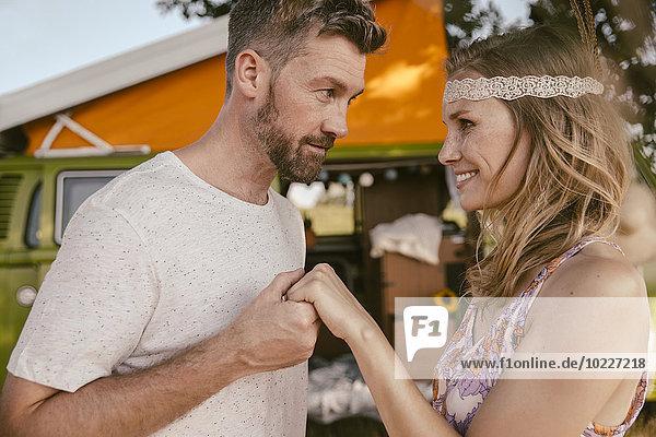 Mann hält Frauenhand vor Van