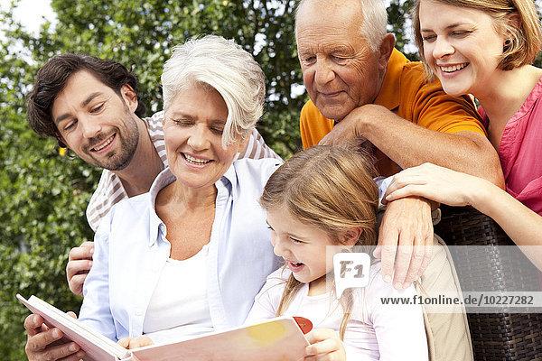 Glückliche Großfamilie mit Buch im Freien