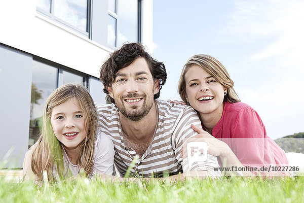 Portrait of happy family lying on lawn